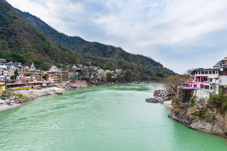 Dramatic sky at Rishikesh, holy town and travel destination in India. Colorful sky and clouds reflecting over the Ganges River.