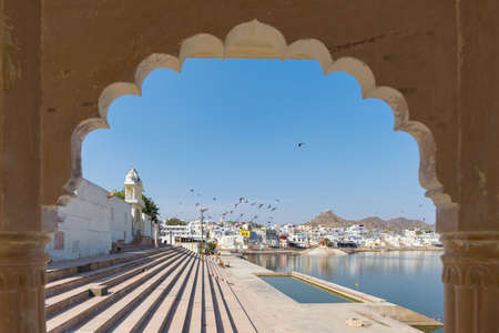 Framed view from archway at Pushkar, Rajasthan, India. Temples, buildings and ghats on the holy water of the lake. Stock Photo