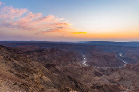 Fish River Canyon, scenic travel destination in Southern Namibia. Last sunlight on the mountain ridges. Wide angle view from above.