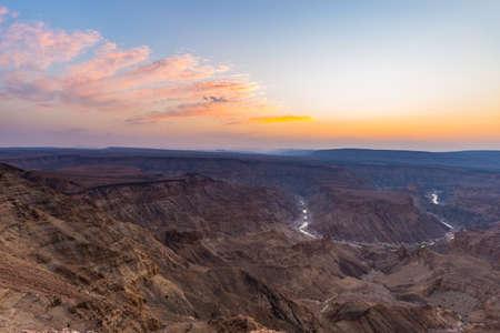 Fish River Canyon, schilderachtige reisbestemming in Zuid-Namibië. Laatste zonlicht op de bergkammen. Groothoekbeeld van boven.