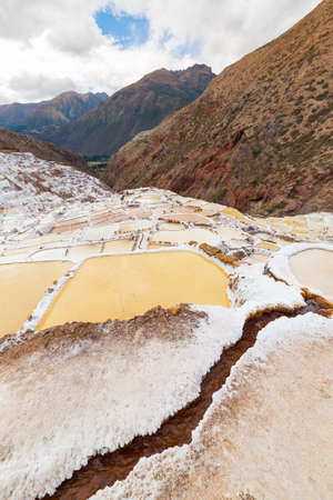 White salt pans also known as Salineras de Maras, among the most scenic travel destination in Cusco Region, Peru. Wide angle view from above with glowing water surfaces and salt ponds.