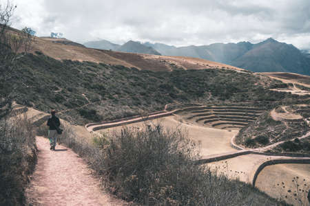 supposed: Tourist exploring the archaeological site at Moray, travel destination in Cusco region and the Sacred Valley, Peru. Majestic concentric terraces, supposed Incas food farming laboratory. Stock Photo