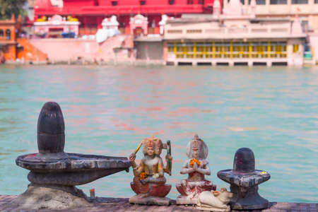 Hindu religion symbols on the bank of the Ganges River, sacred waters. Shiva sculpture and lingam. Defocused temple.