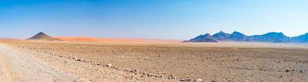 Colorful sand dunes and scenic landscape in the Namib desert, Namib Naukluft National Park, tourist destination in Namibia. Travel adventures in Africa. High resolution panorama. Stock Photo