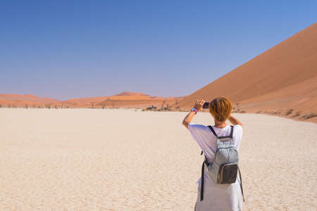 Tourist taking photo with smart phone at Sossusvlei, Namib desert, Namib Naukluft National Park, Namibia. Travel adventure and exploration in Africa. Stock Photo