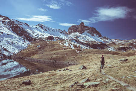 Hiker looking the outstanding view of high altitude landscape and majestic snowcapped mountain peak in autumn season. Wide angle shot in the Italian French Alps. Toned decontrasted image.
