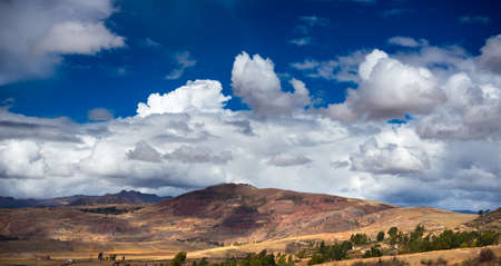 Expansive view of the Sacred Valley, Peru from Pisac Inca site, major travel destination in Cusco region, Peru. Dramatic sky.