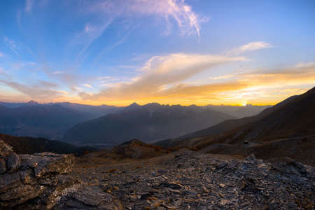 The Italian French Alps at sunset. Colorful sky over the majestic mountain peaks, dry barren terrain and green valleys. Sunburst and backlight expansive view from above.