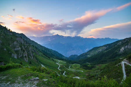 Mountain road leading to high mountain pass on the Italian Alps.. Expasive view at sunset, colorful dramatic sky, adventure road trip in summer.