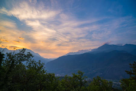 courmayeur: The Italian Alps at sunset. Summer colorful sky over the majestic mountain peaks, woodland and green valleys.