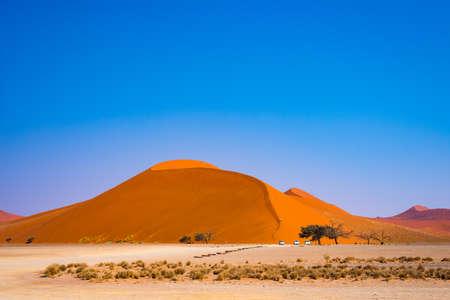 ソーサス フライ、ナミブ砂漠、ナミビア ・ ナミブ ウクルフトパ国立で砂丘を登る観光客。アフリカの人々、冒険と休暇を旅行します。 写真素材