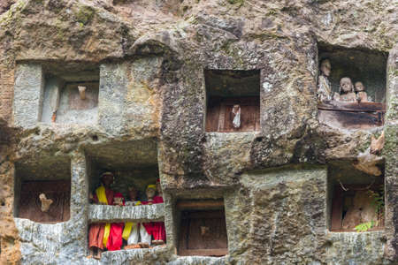 Lemo, Indonesia - september 5, 2014: famous burial site with coffins placed in caves carved into the rock, guarded by the statues of the dead persons (called tau tau in local language). Tana Toraja, South Sulawesi