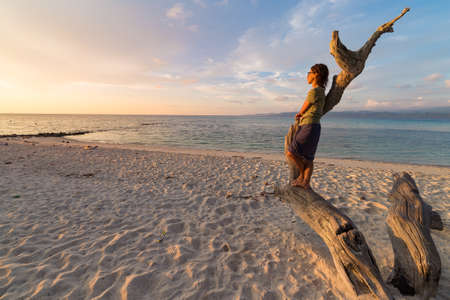 Woman resting on skeletal tree and watching a romantic colorful sunset on the beach of Tanjun Karang, Central Sulawesi, Indonesia. Wide angle shot, long exposure, blurred motion.