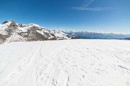 Wide angle view of a ski resort in the distance with elegant mountain peaks arising from the alpine arch in winter season.