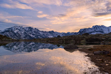 High altitude alpine lake in idyllic landscape. Reflection of snowcapped mountain range and scenic colorful sky at sunset. Wide angle shot taken on the Italian Alps.