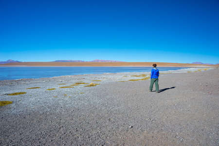 Tourist looking at the stunning landscape of salty frozen lake on the Andes, road trip to the famous Uyuni Salt Flat, travel destination in Bolivia. Stock Photo