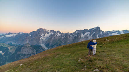 Couple of people looking at the sunrise over Mont Blanc mountain peak (4810 m). Valle dAosta, italian summer adventures and travel destination on the Alps. Stock Photo
