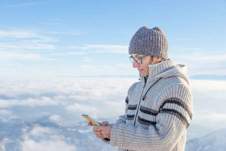 Woman using smart phone on the mountains. Panoramic view of snowcapped Alps in cold winter season. Concept of sharing life moments using new technology.
