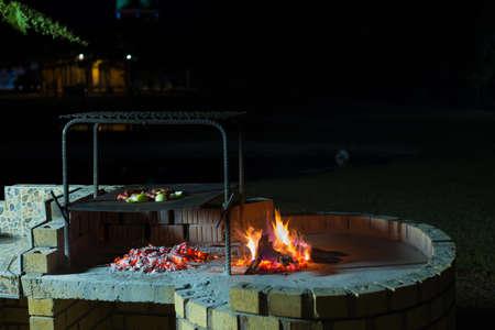 Feu de camp au crépuscule au camping, préparation au barbecue ou au braai, activité en plein air en Afrique du Sud. Mise au point sélective sur le feu et le bois de chauffage. Banque d'images - 93506579