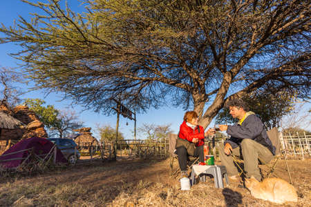 Couple selfie having breakfast, camping outdoors, morning cold. Travel adventure in Kruger National Park, South Africa.