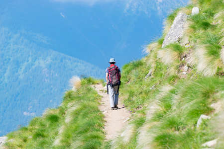 Backpacker walking on hiking trail in the mountain. Summer adventures summer vacation on the Alps. Wanderlust people traveling concept.