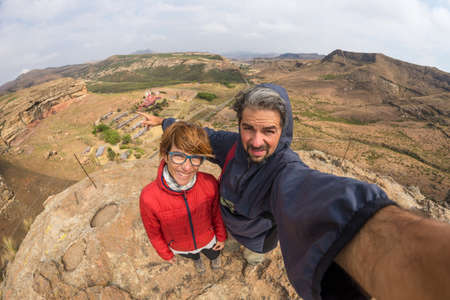 Couple selfie with outstretched arms, wind mountain summit, Golden Gate Highlands National Park, South Africa. Concept of adventure and traveling people. Fish eye view.