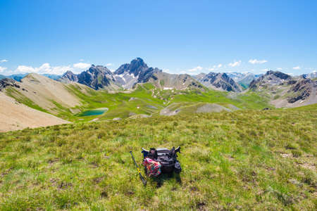 Backpack on mountain top, expansive view on the Alps, summer adventure.