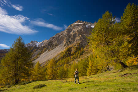Hiker walking on a colorful valley with great panoramic view and vivid colors. Wide angle shot in the Italian French Alps.