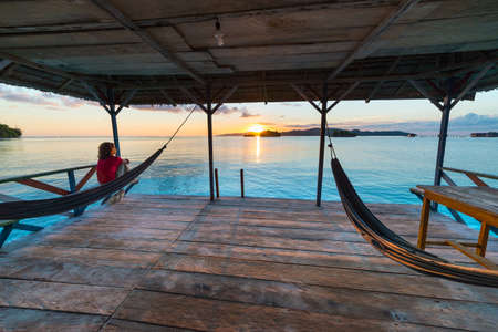 Togean Islands Sunrise, Togian Islands travel destination, Sulawesi, Indonesia. Woman looking at view on hammock, transparent turquoise water with scattered islets. Stock Photo