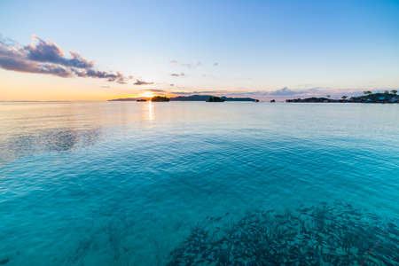 Togean Islands Sunrise, Togian Islands travel destination, Sulawesi, Indonesia. School of fish in transparent turquoise water with scattered islets.