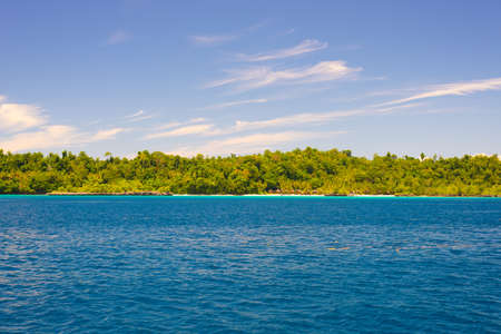 Togian Islands travel destination, Togean Islands scenic beach and coastline with lush green jungle in turquoise sea, Sulawesi, Indonesia.