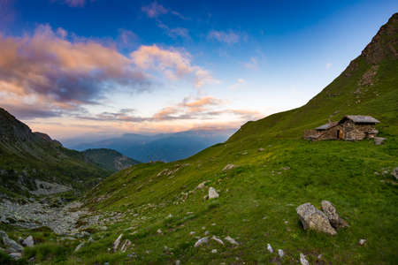 Sunset on the Alps, pasture and meadows with mountain hut refuge, colorful sky.