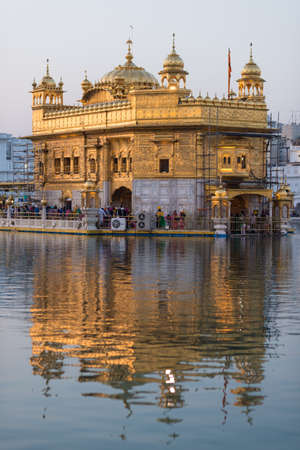 The Golden Temple at Amritsar, Punjab, India, the most sacred icon and worship place of Sikh religion. Sunset light reflected on lake.   Editorial