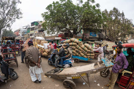 Delhi, India - December 11, 2017: crowd and traffic on street at Chandni Chowk, Old Delhi, famous travel destination in India. Chaotic city life, working people, fisheye ultra wide view. Editorial