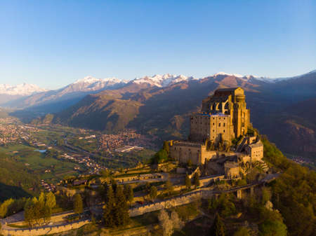 Aerial view old medieval abbey perched on mountain top, background snowy Alps at sunrise. Sacra di San Michele (italian) - Saint Michel Abbey (english traslation) - Turin, Italy