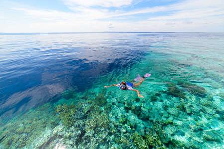Woman snorkeling on coral reef tropical caribbean sea, turquoise blue water. Indonesia Wakatobi archipelago, marine national park, tourist diving travel destination Banco de Imagens