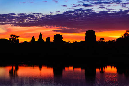 Angkor Wat dramatic sky at dawn main facade silhouette reflection on water pond. World famous temple in Cambodia.