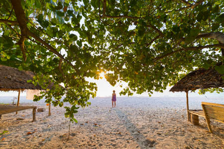 Woman dancing on sand beach romantic sky at sunset, rear view, golden sunlight, real people. Indonesia, Kei islands, Moluccas Maluku