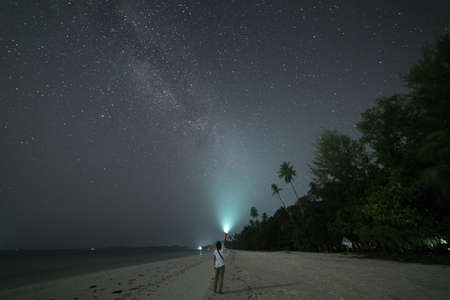 Woman looking at stars and milky way on sand beach, torch light on night sky, rear view, real people. Indonesia, Kei islands, Moluccas Maluku Imagens