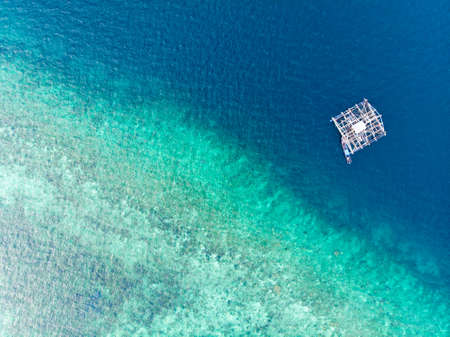 Aerial top down view traditional fishing boat floating on turquoise coral reef tropical caribbean sea. Indonesia Moluccas archipelago, Kei Islands, Banda Sea. Top travel destination, best diving snorkeling. 写真素材 - 122211194