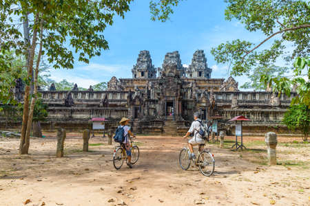 Tourist couple cycling around Angkor temple, Cambodia. Ta Keo building ruins in the jungle. Eco friendly tourism traveling.