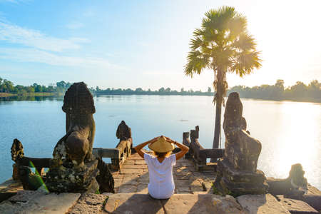 One tourist relaxing in Angkor ruins at sunrise, Srah Srang temple water pond amid jungle, travel destination Cambodia. Woman with traditional hat, rear view. Stock Photo