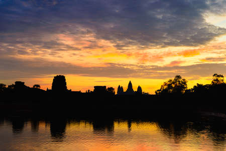 Angkor Wat dramatic sky at dawn main facade silhouette reflection on water pond. World famous temple in Cambodia. 版權商用圖片