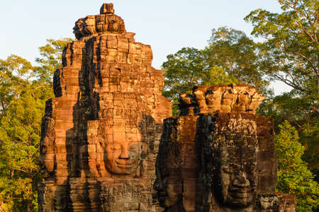 Stone faces in Bayon, Angkor Thom temple, selective focus sunset light. Buddhism meditation concept, world famous travel destination, Cambodia tourism.