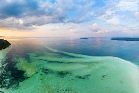 Aerial view tropical beach island reef caribbean sea dramatic sky at sunset sunrise. Indonesia Moluccas archipelago, Kei Islands, Banda Sea. Top travel destination, diving snorkeling