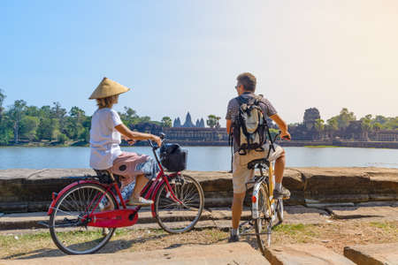 Tourist couple cycling in Angkor temple, Cambodia. Angkor Wat main facade reflected on water pond. Eco friendly tourism traveling. 版權商用圖片