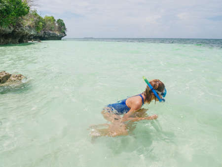Woman snorkeling on coral reef tropical caribbean sea, turquoise blue water. Indonesia Banda archipelago, Moluccas Maluku, tourist diving travel destination