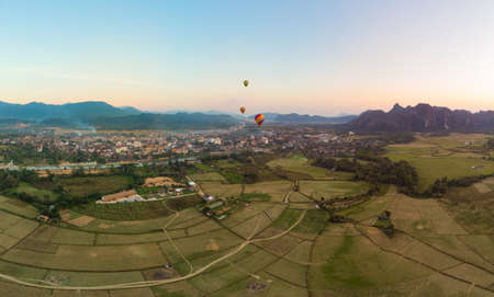 Aerial: Vang Vieng backpacker travel destination in Laos, Asia. Sunset over scenic cliffs and rock pinnacles, rice paddies valley, hot air balloons. Stock Photo