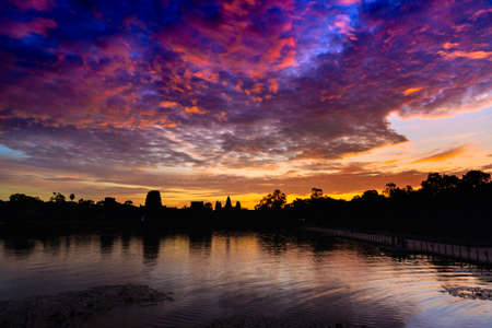Angkor Wat dramatic sky at dawn main facade silhouette reflection on water pond. World famous temple in Cambodia. Stock Photo