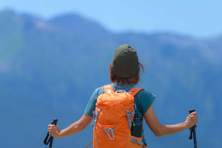 Woman hiker on mountain top with backpack and trekking poles, selective focus rear view, alps in background, summer fitness wellbeing